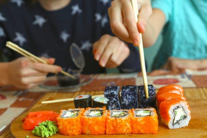 Kids using chopsticks to pick up sushi