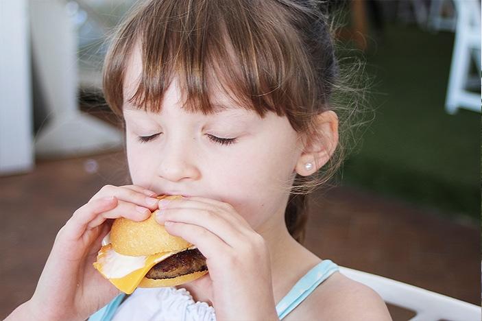 Girl eating mini cheeseburger